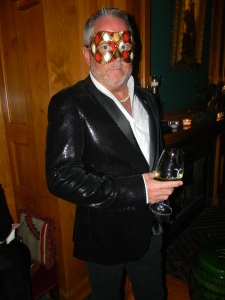 A masked guest from NYC in a tux interpreted in a black sequin jacket at the Caribou charity event